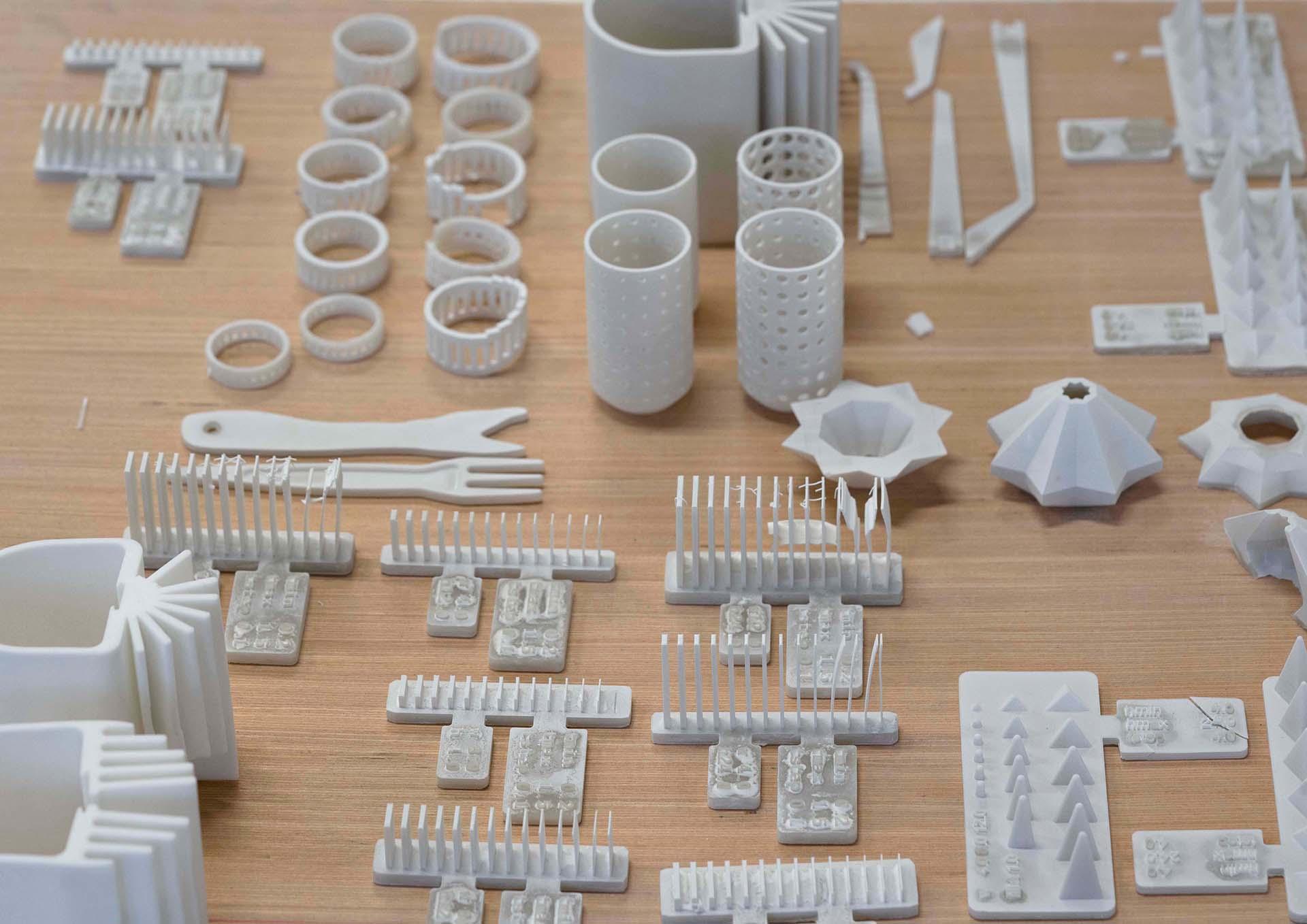 Viele verschiedene gedruckte Keramikteile in Vorbereitung für den Brand und bereits gebrannte Keramiken