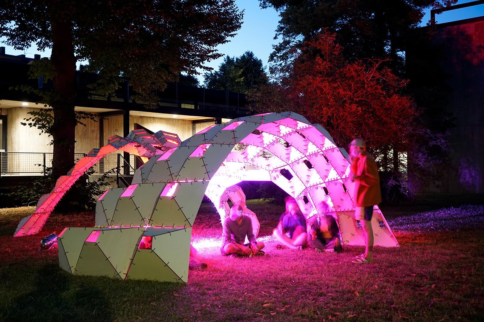 Innenansicht des hell magenta beleuchteten Pavilions mit kleiner Gruppe Feiernder