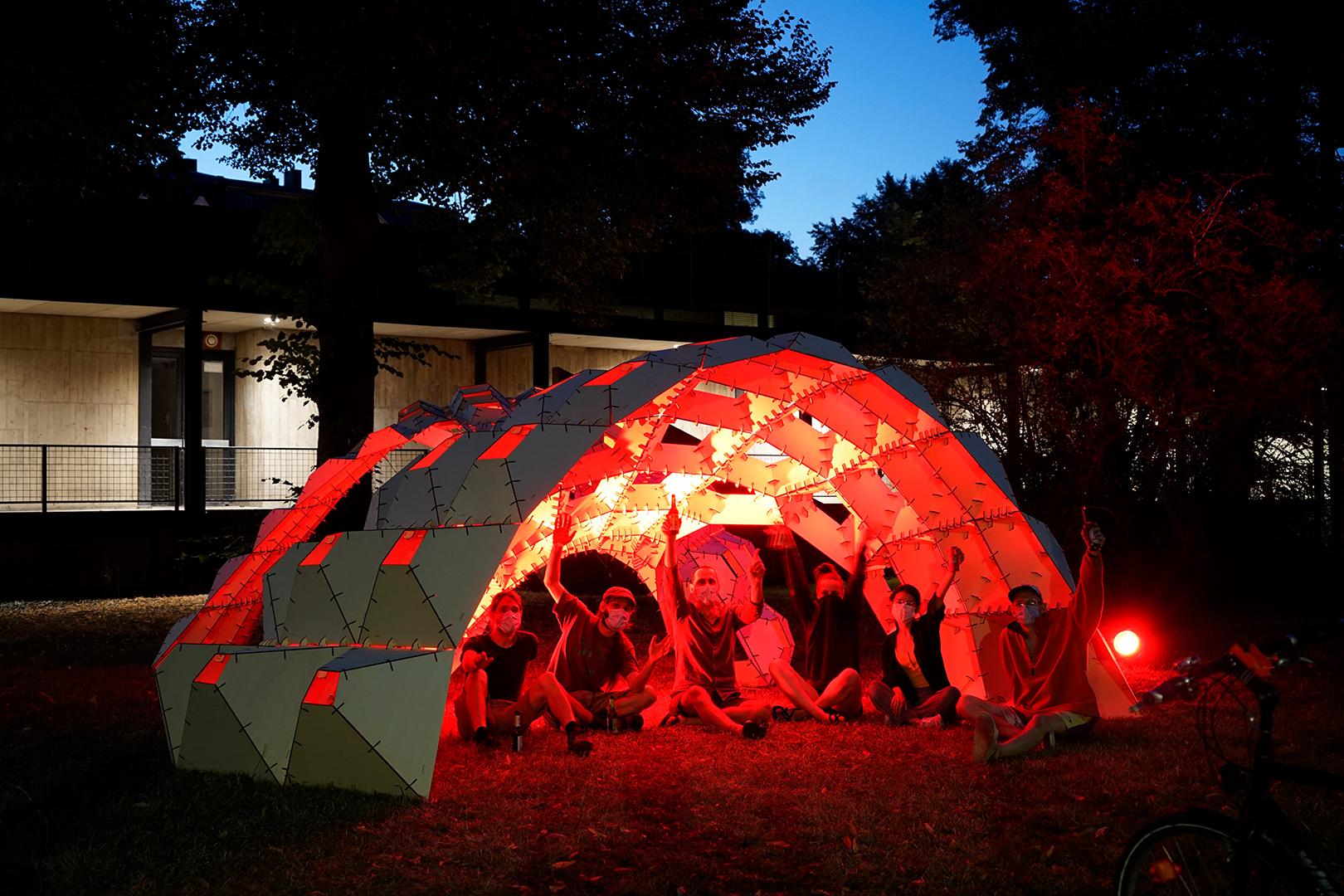 Innenansicht des rot beleuchteten Pavilions mit kleiner Gruppe Feiernder